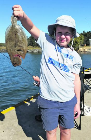 William Lukritz, with this great flounder, is fishing on the school holidays.