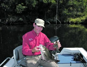The author smiling fondly at a stonker Somerset bass in one hand and a regular sized redclaw in the other.