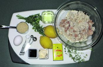 The ingredients for the crab cakes: crab meat, fresh thyme, dry mustard, mayonnaise, Worcestershire sauce, salt, egg, dried breadcrumbs, fresh parsley, canola oil for sautéing, lemon.