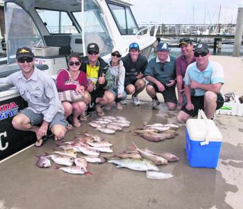 A happy group of anglers with their bag of snapper and a school-sized amberjack.