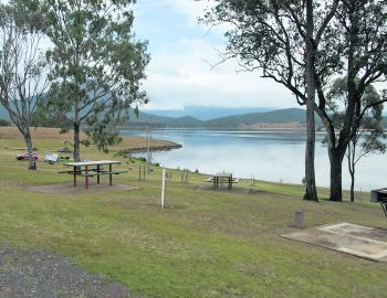 What's not to like about this scenario – handy picnic tables and a wood-fired BBQ with ample camping areas right by the lake.