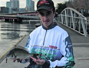 Jason Tanti holding a typical 34cm black bream taken up close to structure.