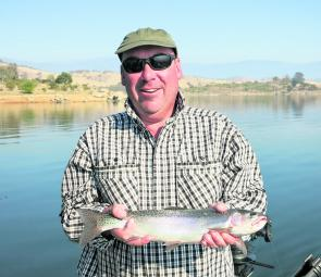 Mark Allan with a decent Jindabyne rainbow caught trolling a frog pattern Tasmanian Devil lure.