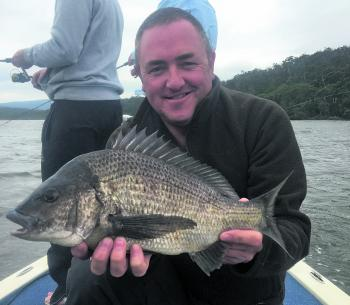 Jason Neuman with a cracking black bream caught from the shallows on a very windy day.
